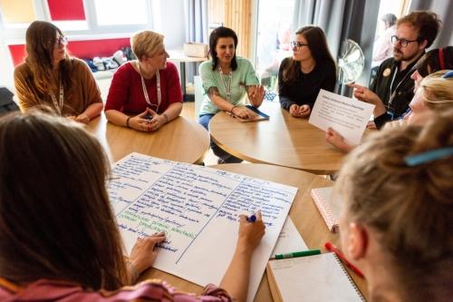 Uczestnicy warsztatów rozmawiają przy okrągłym stole, część z nich pisze wnioski z dyskusji na dużej kartce