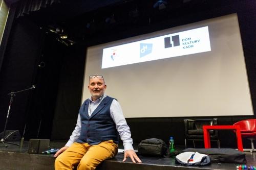 Jacek Gralczyk siedzi na scenie i prowadzi wykład inaugurujący konferencję