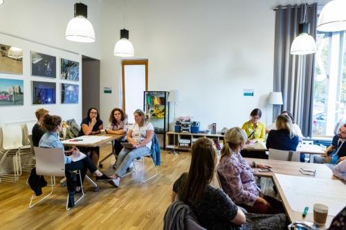 uczestnicy podczas warsztatów przy kwadratowych stołach