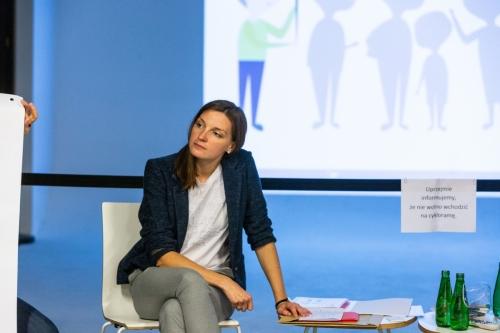 Prowadząca warsztaty siedzi na krześle w tle wyświetlona na ekranie prezentacja