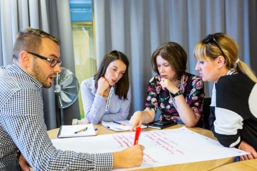 uczestnicy warsztatów dyskutują i wnioski spisują na planszy, która leży na stole