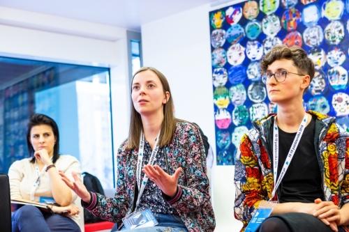 Kobieta wypowiada się podczas warsztatów, dwie uczestniczki słuchają