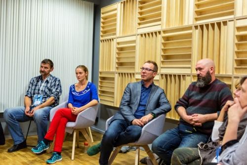 uczestnicy warsztatów siedzą na krzesłach pod ścianą