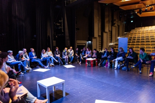 Uczestnicy warsztatów siedzą na krzesłach ustawionych w koło. Warsztaty odbywają się na scenie w sali widowiskowej.